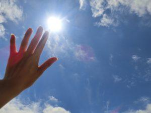 太陽に向かって手をかざす